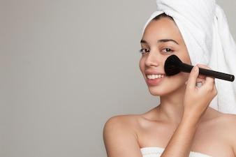 Smiley woman using facial make up