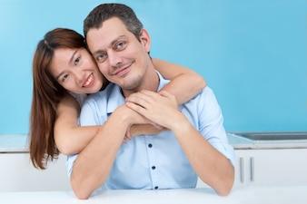 夫、キッチンに抱き合っている笑顔のアジア人女性