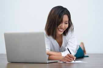 Smiling Asian Woman Writing on Floor with Laptop