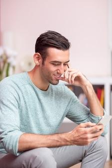Улыбающийся привлекательный человек с помощью смартфона дома