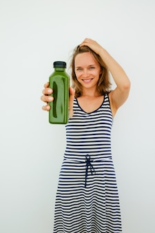 Smiling beautiful young woman using natural shampoo and showing product to camera. Happy girl drinking smoothie to be healthy. Choice concept