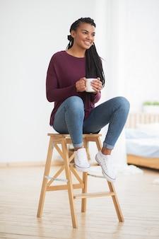 Smiling black woman with mug sitting on stool