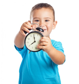 Smiling boy showing with an alarm clock