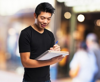 Smiling boy with notebook and pen
