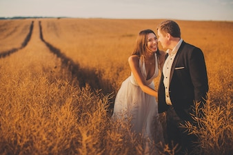 Smiling bride and groom standing in field
