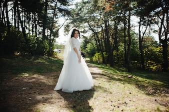 屋外に立つ笑顔のブルネットの花嫁