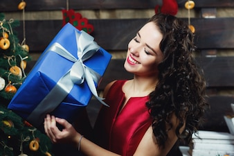 Smiling brunette holds blue present box standing before Christmas tree