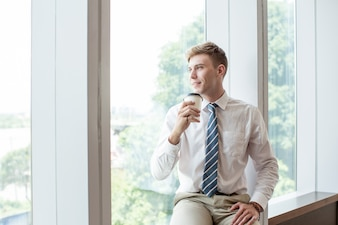 Smiling Business Man Drinking on Window Sill