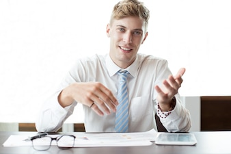 Smiling Business Man Gesturing at Office Desk