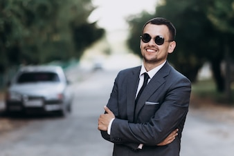 Smiling businessman in suit standing outdoors. Success concept