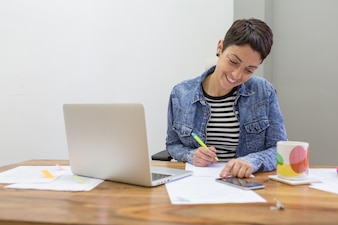 Smiling businesswoman signing a document
