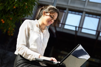 Smiling businesswoman typing on laptop