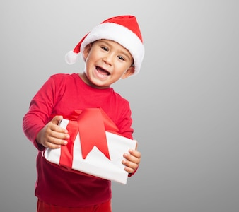 Smiling child holding a gift with decorative ribbon