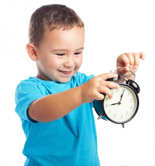 Smiling child looking at an alarm clock