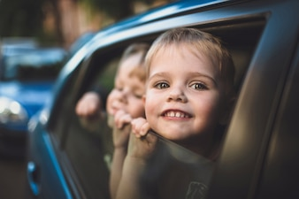 Smiling child looking out of a car window