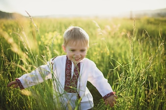 Smiling child walking by a green field