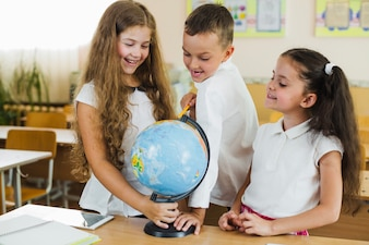 Smiling children having fun with globe