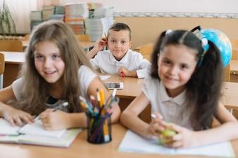 Smiling children sitting in classroom at desks.