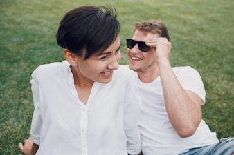 Smiling couple lies on the green lawn