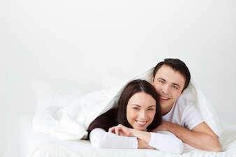 Smiling couple lying in bed