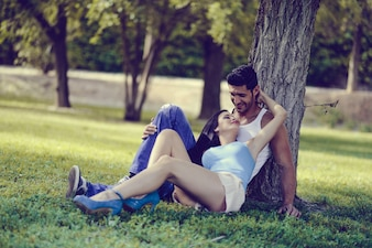 Smiling couple lying on the grass in a park