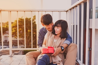 Smiling couple sitting on the floor with a red gift