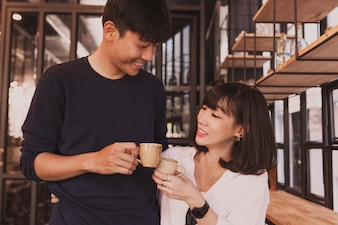 Smiling couple toasting with cups of coffee