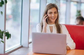 Smiling elegant woman talking on the phone and the screen of her computer