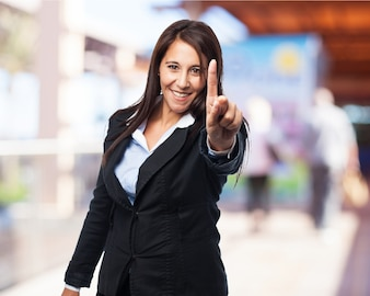 Smiling elegant woman with a raised finger