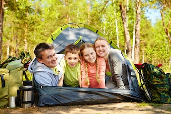 Smiling family in the tent on sunny meadow