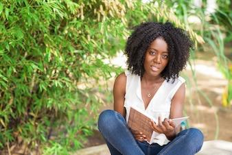 屋外で本に座っている笑顔の女性の学生