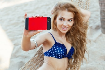 Smiling girl holding a mobile phone and taking photo