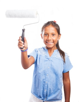 Smiling girl holding a paint roller