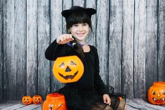 Smiling girl holding trick or treat basket