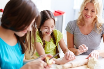 Smiling girl kneading pizza dough