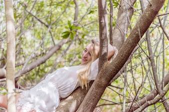 Smiling girl lying on a tree