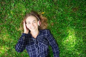 Smiling Girl Lying on Grass and Wearing Headphones