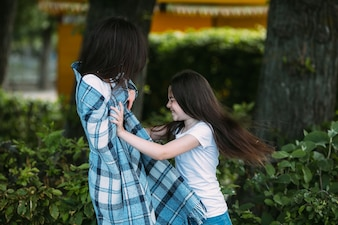 Smiling girl pushing woman wrapped in plaid
