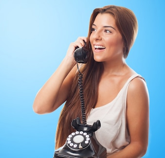 Smiling girl talking over old-fashioned phone