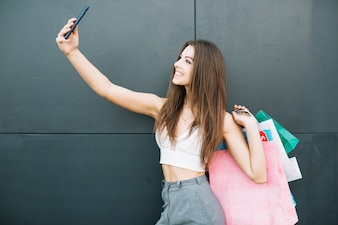 Smiling girl with bags making selfie