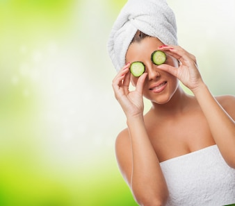 Smiling girl with towel on head and cucumbers on eyes