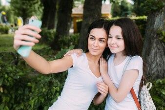 Smiling girls hugging taking selfie
