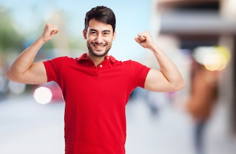 Smiling guy showing his muscles