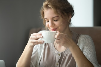 Smiling happy woman drinking aromatic coffee with closed eyes