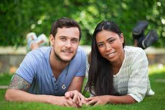 Smiling Interracial Couple Relaxing on Patio Grass
