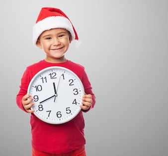 Smiling kid holding a clock