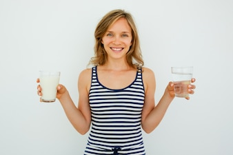 Smiling Lady Holding Glasses of Water and Milk