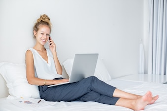 Smiling Lady Talking on Phone on Bed With Laptop