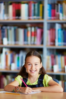 Smiling little girl drawing in the library