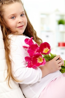 Smiling little girl holding a bouquet